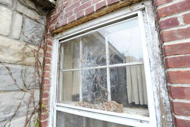 A dirty window at the Greenwich Emergency Medical Service's location at 1327 King St., that was damaged during Superstorm Sandy last month,Tuesday afternoon, Nov. 20, 2012. The town's Building Department has condemned the structure. Photo: Bob Luckey / Greenwich Time