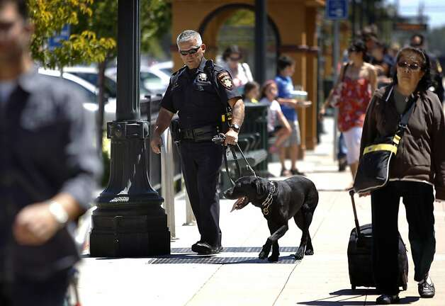 Deputy Bruce McKay patrols the Burlingame Caltrain station with his four-legged partner, Shakhor. Photo: Paul Chinn, The Chronicle