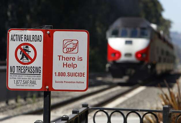 Caltrain signs attempt to reach out to suicidal people along the tracks in Burlingame and elsewhere. Photo: Paul Chinn, The Chronicle