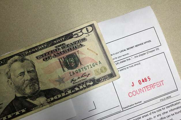 Counterfeits like this fake $50 often go unnoticed by cashiers when lines of impatient customers are waiting. During the holidays, Secret Service agents see an increase in counterfeiting. Photo: Lea Suzuki, The Chronicle