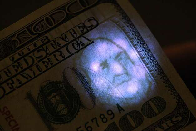 A black light illuminates the watermark on a real $100 bill at the S.F. office of the U.S. Secret Service - an agency created to combat counterfeiting. Photo: Lea Suzuki, The Chronicle