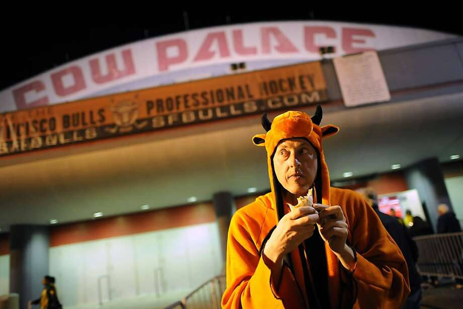 "Above: Dressed in his custom-made costume in honor of the San Francisco Bulls, ""unofficial mascot"" Jay Bergers III of San Francisco eats a burrito before a minor-league hockey game at the Cow Palace in Daly City. Photo: Michael Short, Special To The Chronicle"
