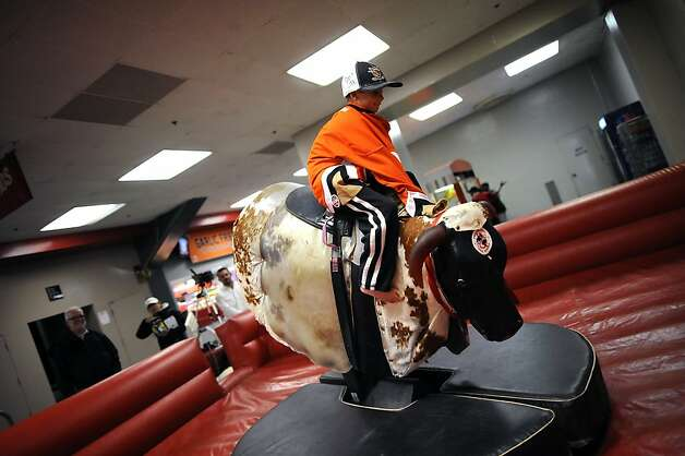 Riley Goodman, a 9-year-old from San Francisco, rides a mechanical bull in the concourse before the game. Photo: Michael Short, Special To The Chronicle