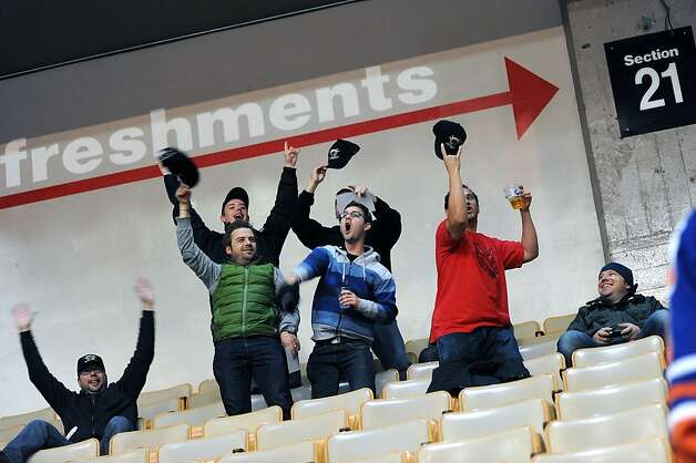 A group of fans dance enthusiastically as they are put up on the big screen over center ice for everyone to see.  The new minor league hockey team the San Francisco Bulls played the Stockton Thunder at the Cow Palace in San Francisco, CA, Friday November 9th, 2012. Photo: Michael Short, Special To The Chronicle