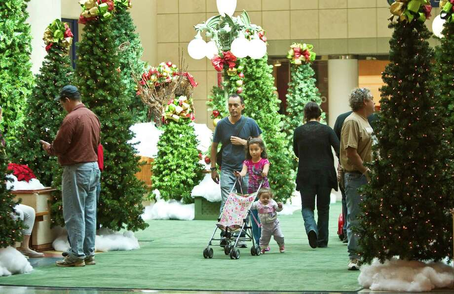 Julio Carlos, of Torreon Mexico, center, walks with his niece Sofia Navarro, 7, of South Houston, and daughter Ana Camila Carlos, 15-months, through a Christmas tree exhibit at the Baybrook Mall Monday, Nov. 19, 2012,  in Friendswood. ( Nick de la Torre / Houston Chronicle ) Photo: Nick De La Torre, Staff / © 2012  Houston Chronicle