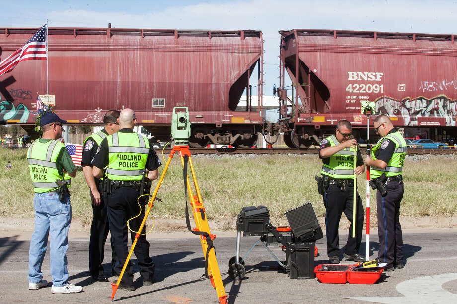 Midland Police officers prepare to reconstruct the scene of a train accident Tuesday, Nov. 20, 2012 at the intersection of Industrial Avenue and Garfield Street in Midland, Texas. Four Military veterans died when a train collided into a float during a parade Thursday, Nov. 15, 2012 at that intersection. (AP Photo/Odessa American, Albert Cesare) Photo: Albert Cesare, Associated Press / Odessa American