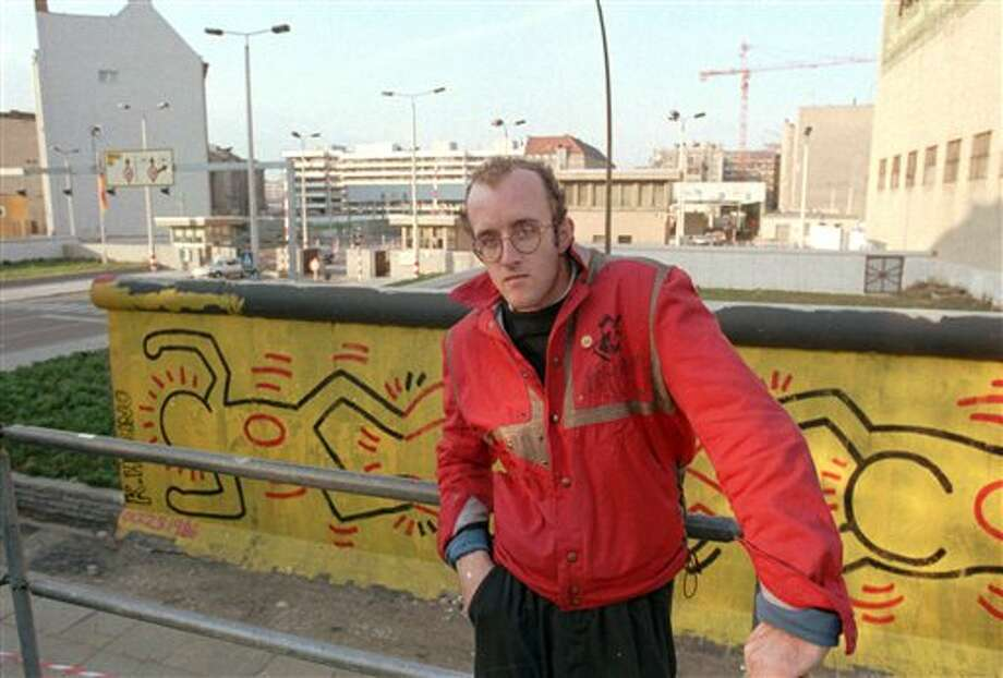 In this October 1986 file photo, artist Keith Haring stands in front of part of the Berlin Wall that he painted with a crawling baby in Berlin. The Berlin Wall came down in late 1989. Haring died of AIDS Feb. 16, 1990, at age 31. Photo: Elke Bruhn-Hoffmann, AP File Photo / AP1996