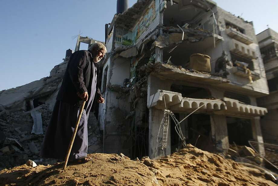 An elderly Palestinian walks next to a destroyed building after an Israeli strike in Gaza City, Tuesday, Nov. 20, 2012. Efforts to end a week-old convulsion of Israeli-Palestinian violence drew in the world's top diplomats on Tuesday, with President Barack Obama dispatching his secretary of state to the region on an emergency mission and the U.N. chief appealing from Cairo for an immediate cease-fire. Photo: Hatem Moussa, Associated Press