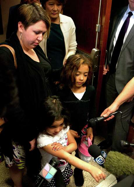 "Makayla Dickerson shows her ""pretty arm"" as she stands with her mom Tiffany Dickerson, left, and sister Kiyanna Richardson after Jessica Tata's sentencing Tuesday, Nov. 20, 2012, in Houston. Tata was sentenced to 80 years for her felony murder conviction in the death of one of four children killed in a fire at her home day care in Houston. (AP Photo/Houston Chronicle, Cody Duty) Photo: Cody Duty, MBI / Houston Chronicle"