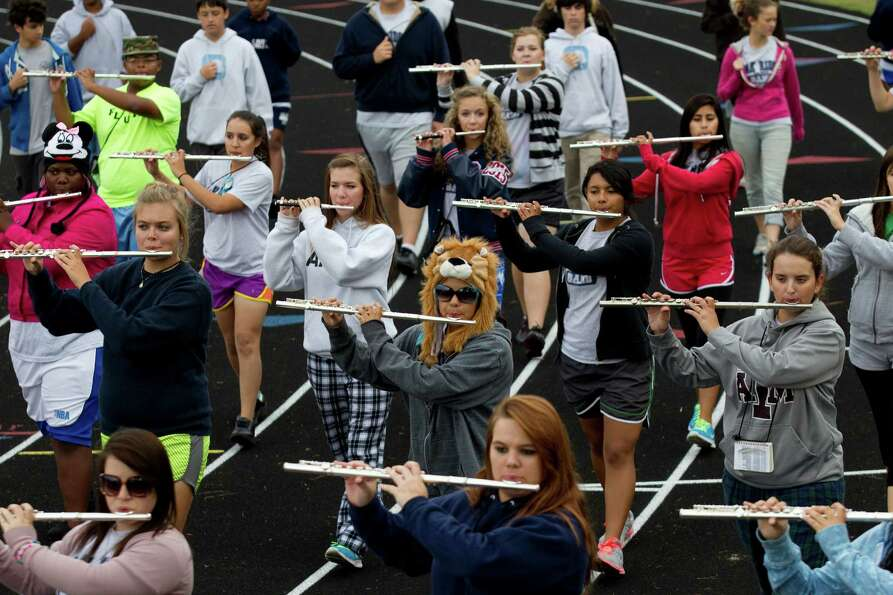 The Oak Ridge High School Band flute section marches along the school's track while preparing to mar
