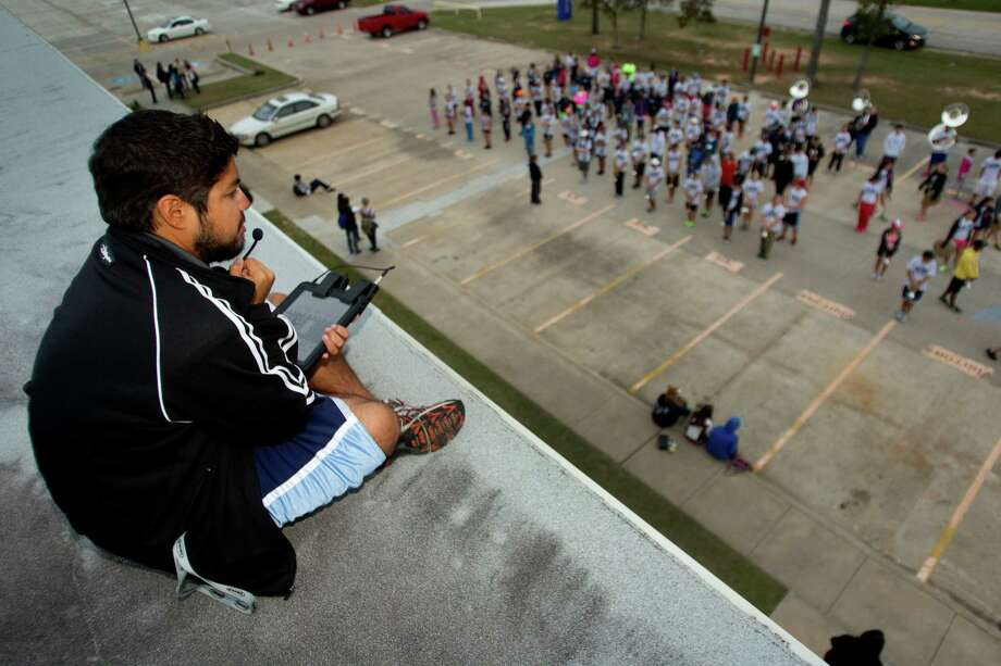 Albert Vela, assistant band director, sits on the roof at Oak Ridge High School as he oversees rehearsals as the band prepares to march in the Macy's Thanksgiving Day Parade Tuesday, Nov. 13, 2012, in Conroe. Photo: Brett Coomer, Houston Chronicle / © 2012 Houston Chronicle