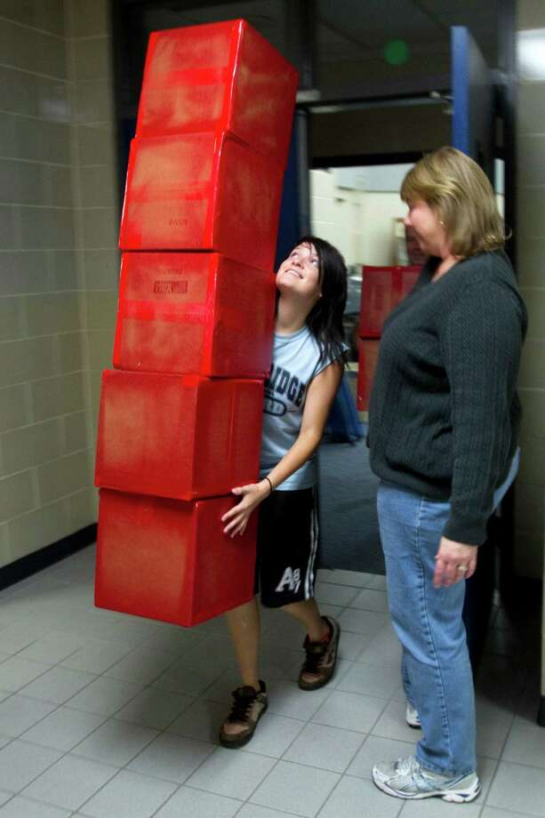Courtney Cole, an Oak Ridge High School color guard member, left, walks past Karen Perez with a stack of boxes to be decorated into presents for the color guard to carry in the Macy's Thanksgiving Day Parade Wednesday, Nov. 14, 2012, in Conroe. Photo: Brett Coomer, Houston Chronicle / © 2012 Houston Chronicle