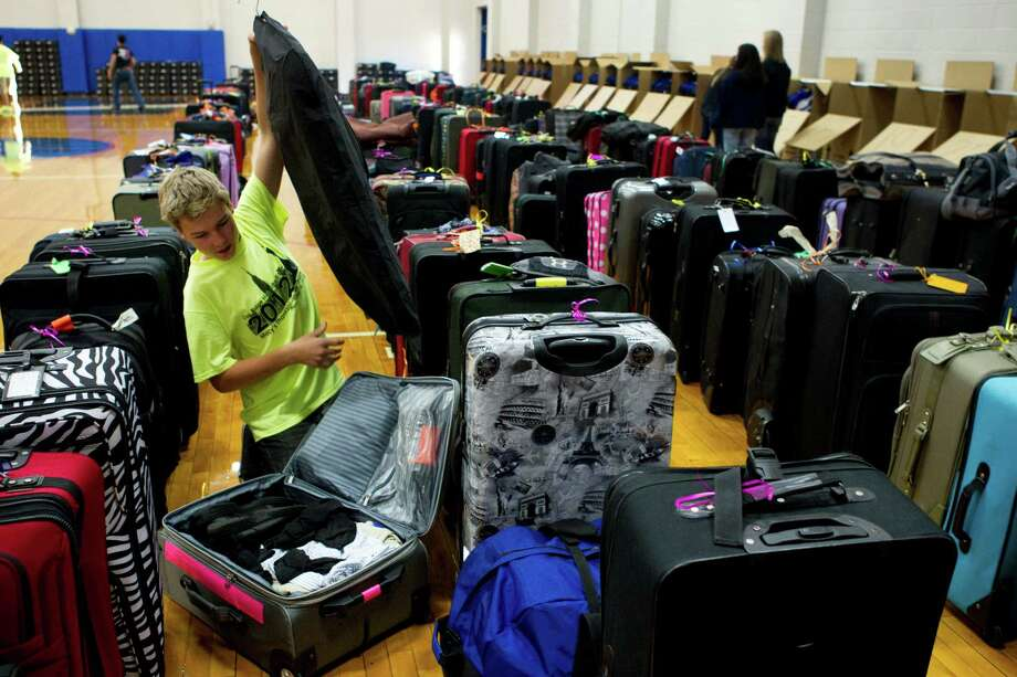 Austin Oliver does a bit of last-minute packing as he sits surrounded by his bandmates' luggage as the Oak Ridge High School Band prepare for the trip to New York City to march the Macy's Thanksgiving Day Parade Tuesday, Nov. 16, 2012, in Conroe. Photo: Brett Coomer, Houston Chronicle / © 2012 Houston Chronicle