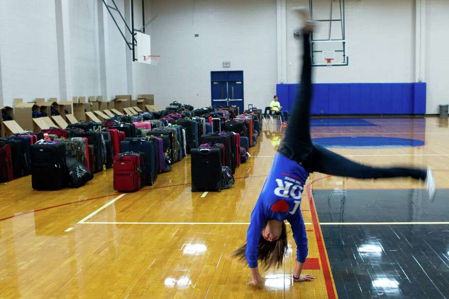 Abby Tennison does a cartwheel in front of her bandmates' luggage as the Oak Ridge High School Band prepare for the trip to New York City to march the Macy's Thanksgiving Day Parade Tuesday, Nov. 16, 2012, in Conroe. Photo: Brett Coomer, Houston Chronicle / © 2012 Houston Chronicle