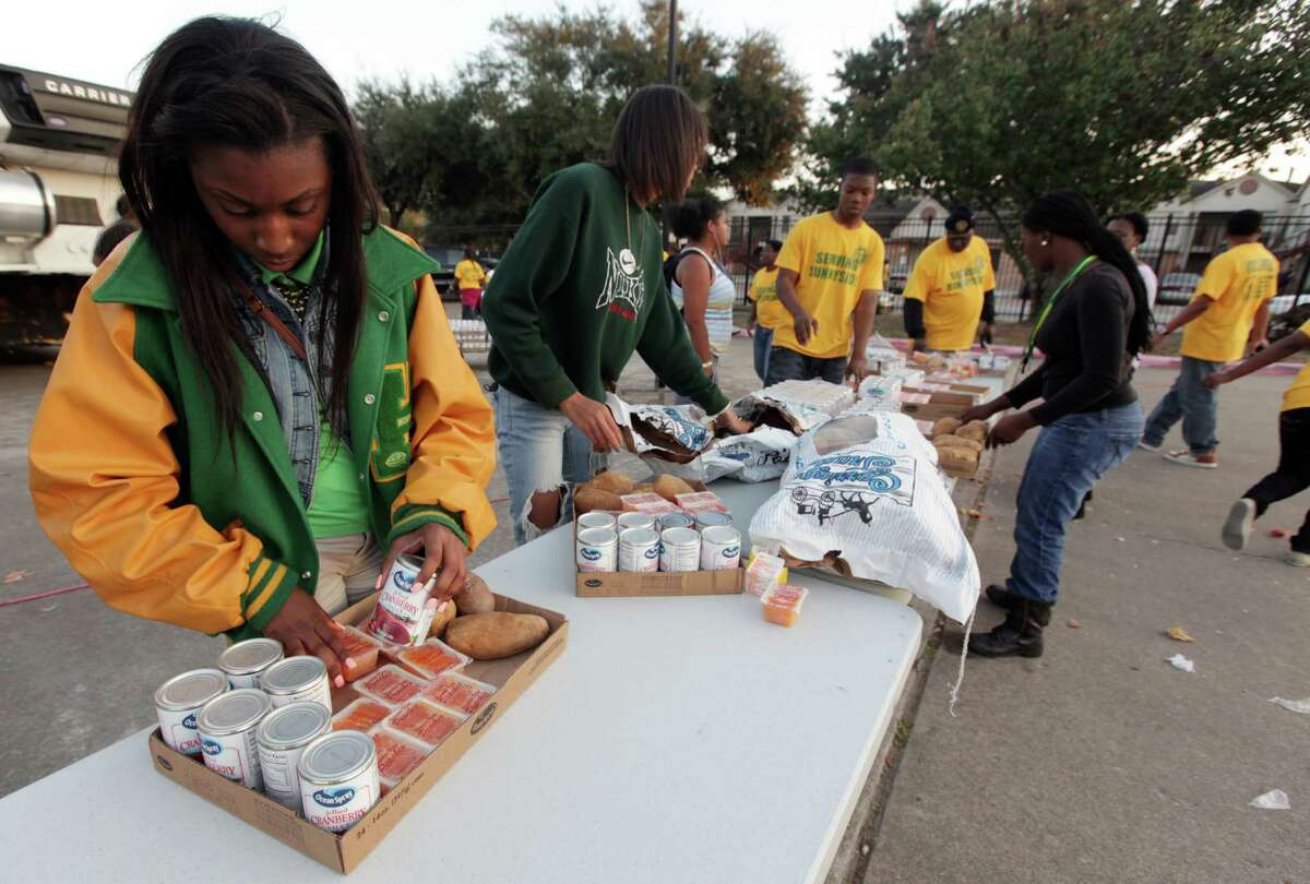 Jaelin Fields, 18, arranges a Thanksgiving food basket as the Houston Area Urban League and Worthing High School students feed approximately 200 families in the Sunnyside Community on Tuesday, Nov. 20, 2012, in Houston.