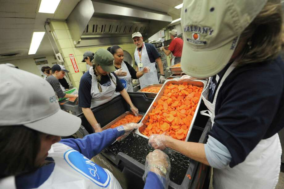 Volunteer chef Mark McDonald, center,oversees a group of volunteers prepping carrots for the Equinox Thanksgiving Dinner at the Empire State Plaza in  Albany, NY Tuesday Nov. 20, 2012. (Michael P. Farrell/Times Union) Photo: Michael P. Farrell