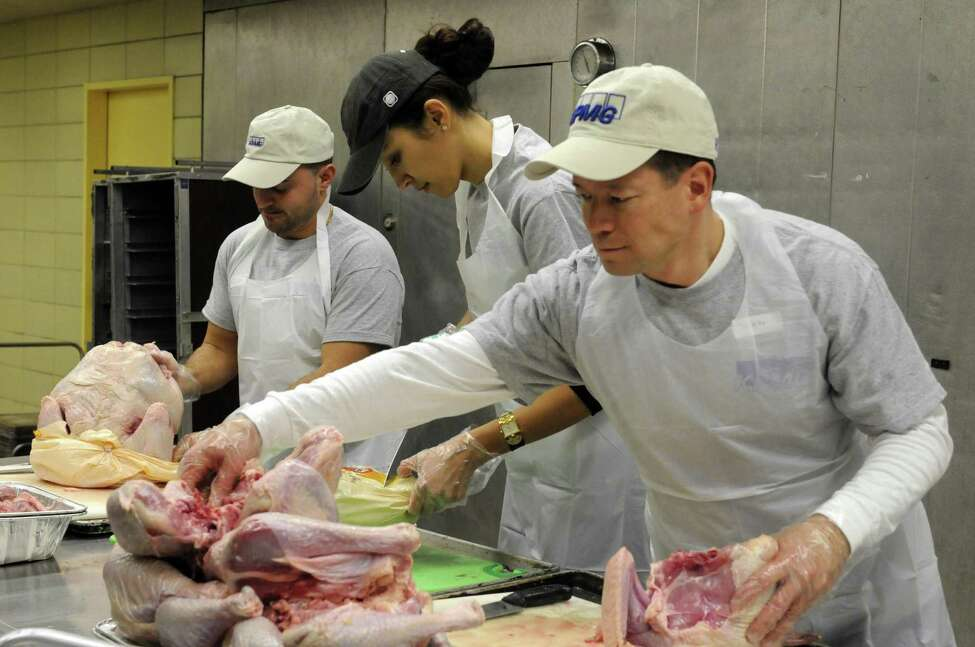 Volunteer from KPMG, left to right, Dominick Caldarazzo, Zamira Akchurina and Dean Geesler prep turkey for the Equinox Thanksgiving Dinner at the Empire State Plaza in Albany, NY Tuesday Nov. 20, 2012. (Michael P. Farrell/Times Union)