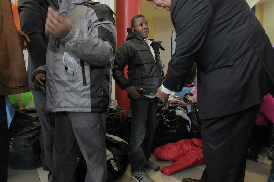 Fourth grader Gregory Corpening, center, 10, gets help trying on a coat by Albany Mayor Gerald Jenni
