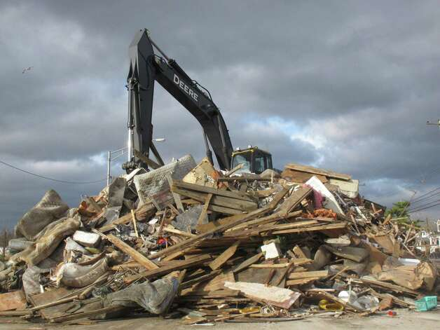 A crane sits atop a pile of storm debris in a parking lot in Point Pleasant Beach N.J. on Nov. 15, 2012. Superstorm Sandy created tons of debris that towns in New York and New Jersey are still struggling to dispose of weeks later. Three weeks in, the round-the clock effort to remove storm rubble has strained the resources of sanitation departments and landfill operators, and caused heartaches and headaches for thousands of families.  (AP Photo/Wayne Parry) Photo: Wayne Parry