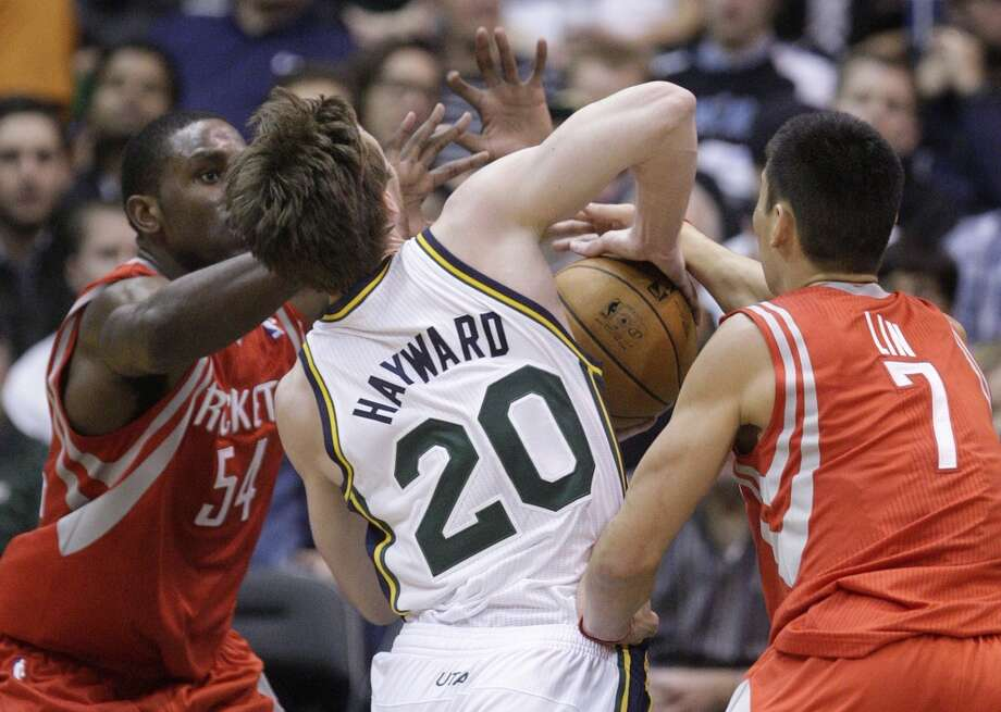 Patrick Patterson and Jeremy Lin of the Rockets defend Gordon Hayward of the Jazz. (Rick Bowmer  / Associated Press)