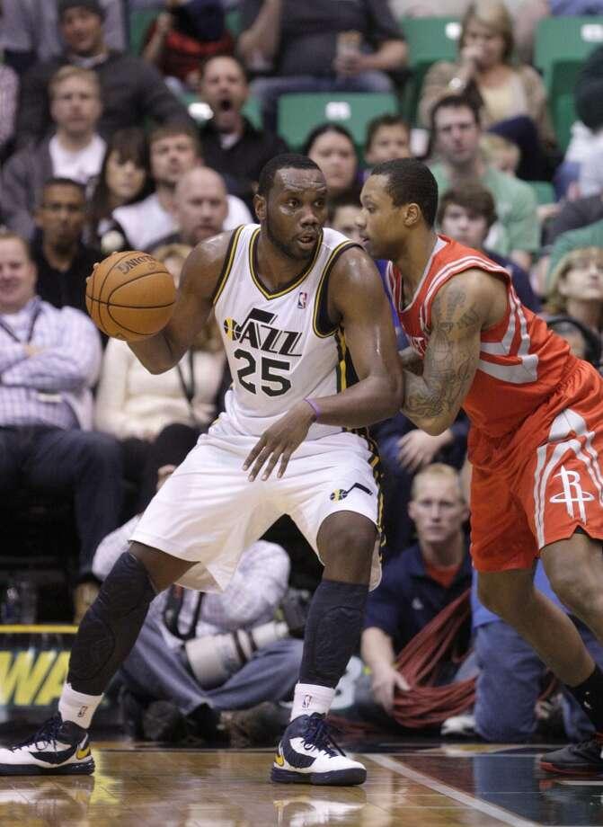 Jazz center Al Jefferson posts up Greg Smith of the Rockets.  (Rick Bowmer / Associated Press)