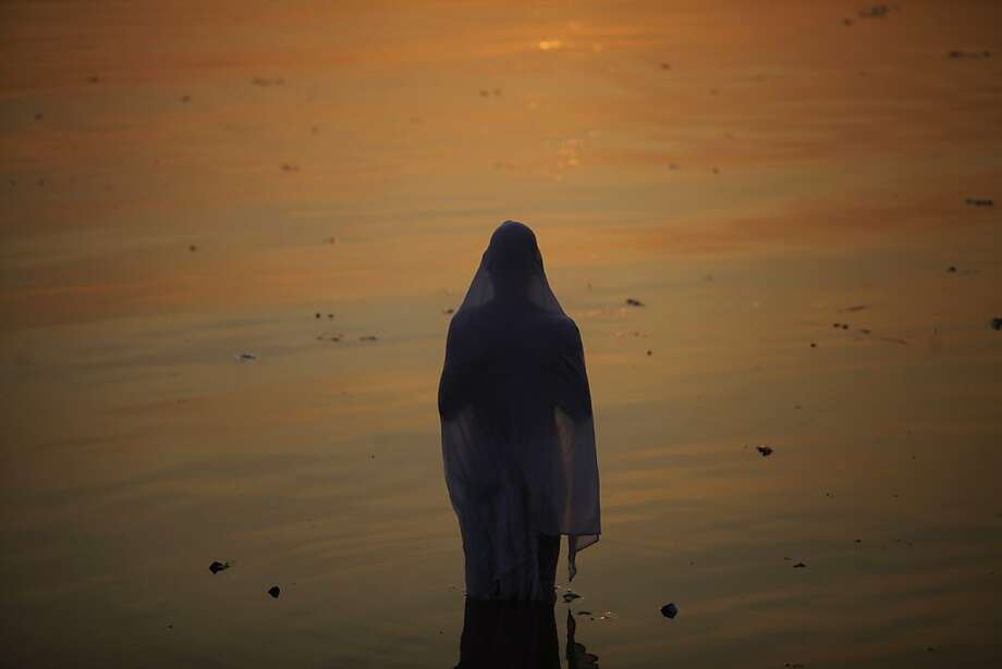 An Indian Hindu devotee performs rituals at sunset during Chhath Puja festival, in the Hussan Sagar Lake (Tankbund) in Hyderabad, India, Monday, Nov. 19, 2012. On Chhath, an ancient Hindu festival, rituals are performed to thank the Sun God for sustaining life on earth. Photo: Mahesh Kumar A, Associated Press