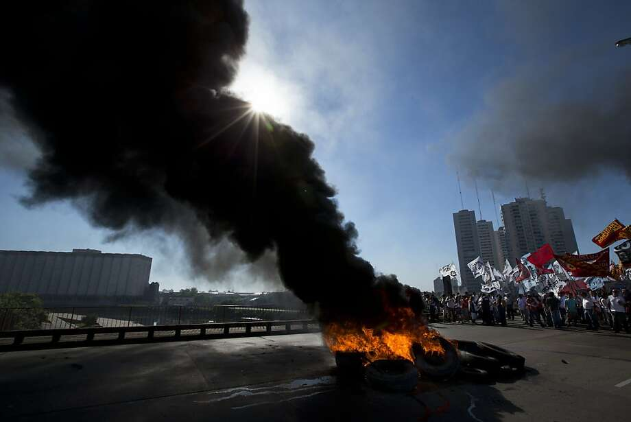 Workers burn tires to block a bridge that leads to the capital during a 24-hour general strike in Buenos Aires, Argentina, Tuesday, Nov. 20, 2012.  Argentine President Cristina Fernandez is facing a nationwide strike, led by union bosses who once were her most steadfast supporters. Many trains and bus lines are paralyzed; banks, courts and schools are closed; airlines have canceled flights and small groups of people have blocked highways in about a dozen places around the capital. Photo: Victor R. Caivano, Associated Press