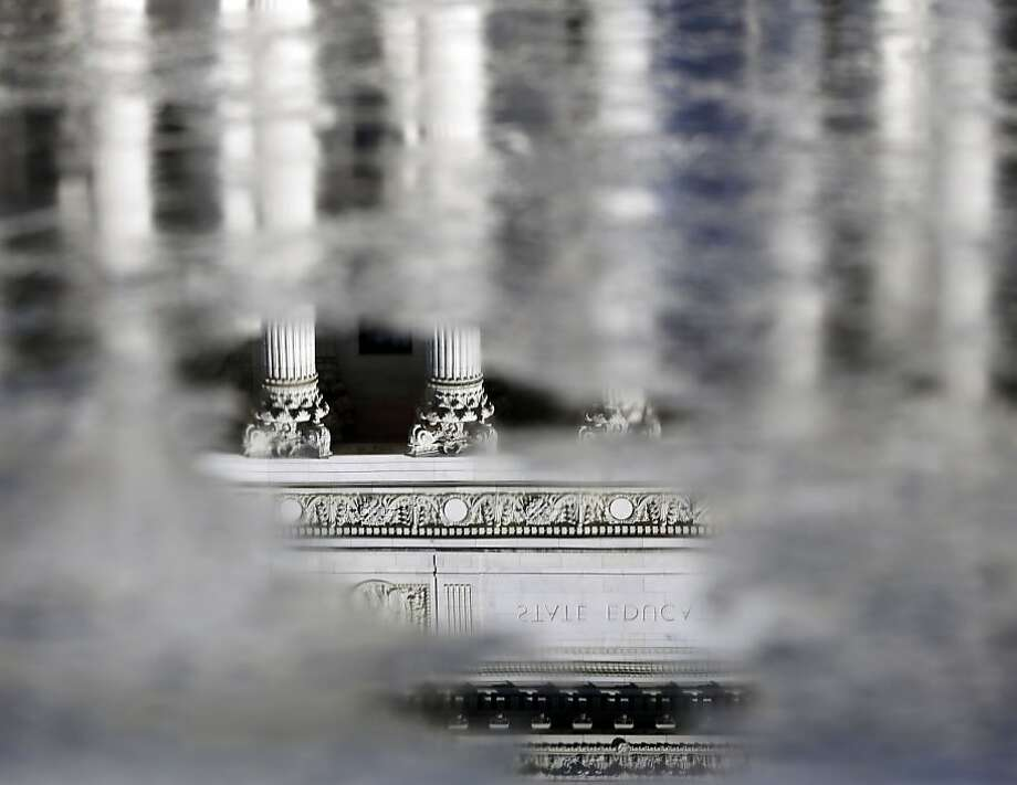 A partially frozen fountainreflects the State Education Building in Albany, N.Y. Photo: Mike Groll, Associated Press