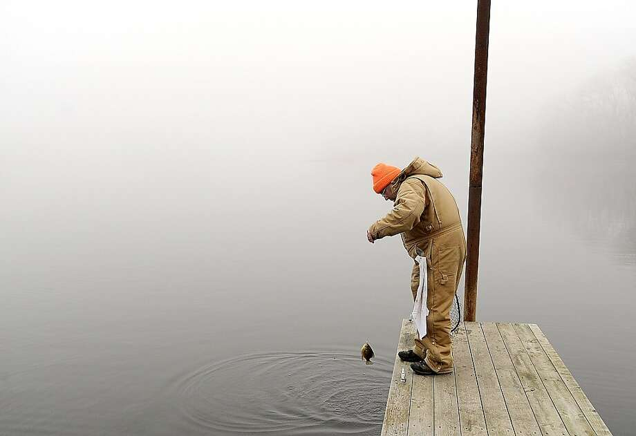 Jim Winistorfer of Winona pulls up a small sunfish while fishing in dense fog Tuesday, Nov. 20, 2012, morning on the docks at Minnesota City Boat Club in Minnesota City, Minn. While jigging for sunfish and crappies, Jim said he fishes as much as he can, mostly on the backwaters and main channel of the Mississippi River. Photo: Andrew Link, Associated Press