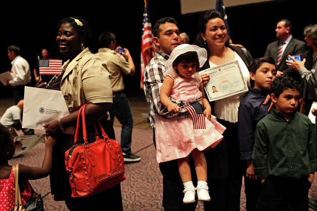 Marlon Ruiz, right, his wife, new U.S. citizen Lisette Ruiz, and their children, Lisette, 2, from left, Marlon, Jr., 8, and Angel, 6, pose for pictures after the Naturalization Ceremony for almost 900 new U.S. citizens, including Lisette, in Laurie Auditorium at Trinity University in San Antonio on Tuesday, Nov. 20, 2012. At left, new U.S. citizen Adelaide Mensah-Peprah, originally from Ghana, poses for her family to take a pictures of her as well. Photo: Lisa Krantz, San Antonio Express-News / © 2012 San Antonio Express-News