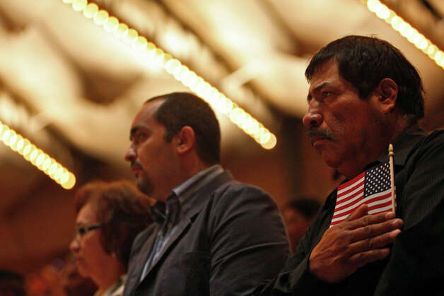 New U.S. citizen Jose Estrada, right, stands during the Posting of the Colors during the Naturalization Ceremony for new U.S. citizens in Laurie Auditorium at Trinity University in San Antonio on Tuesday, Nov. 20, 2012. Photo: Lisa Krantz, San Antonio Express-News / © 2012 San Antonio Express-News