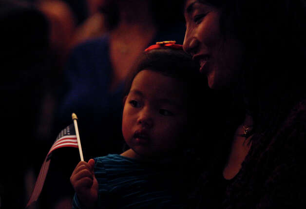 New U.S. citizen Su Chun, from South Korea, holds her daughter, Emily Chun, 2, who was born in the U.S., during the Naturalization Ceremony where almost 900 new U.S. Citizens, including Chun, were naturalized, in Laurie Auditorium at Trinity University in San Antonio on Tuesday, Nov. 20, 2012. Photo: Lisa Krantz, San Antonio Express-News / © 2012 San Antonio Express-News