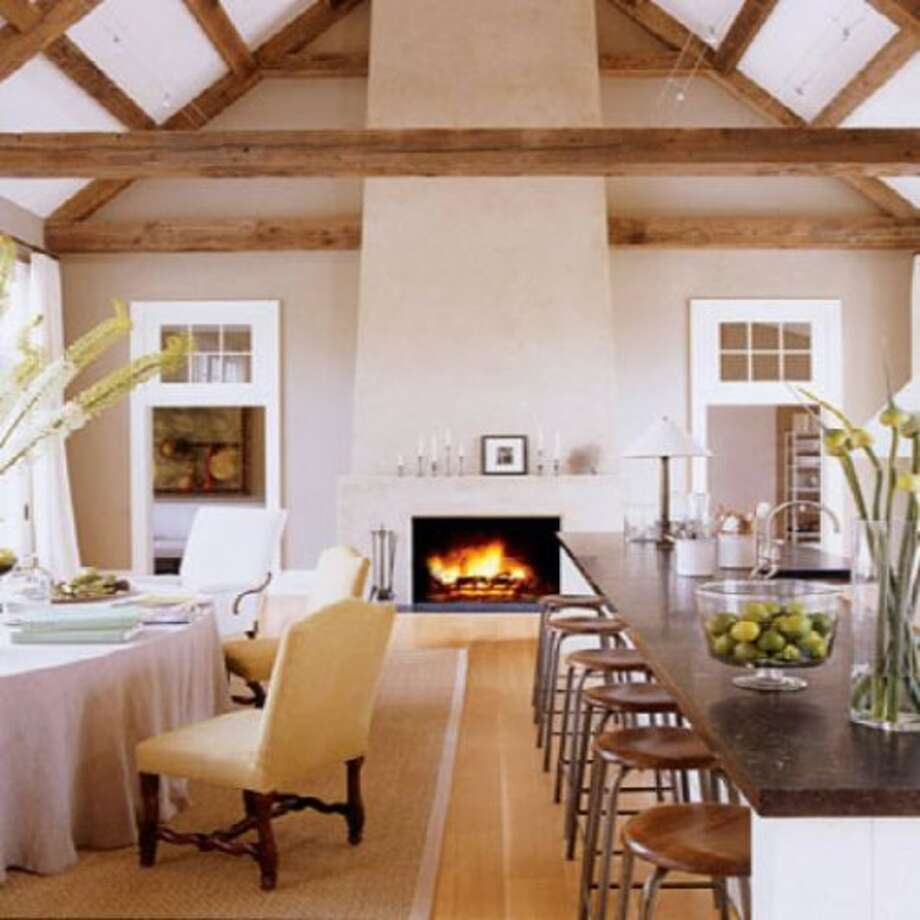 Ina Garten hosts her show from her home in the Hamptons. While it's been some time since I've seen her show, the kitchen pictures do resemble the kitchen from her show. A true entertaining chef, her island counter top seats 6, a round dining table is just off to the side and this is all around a warm and cozy fireplace. (curbed.com)