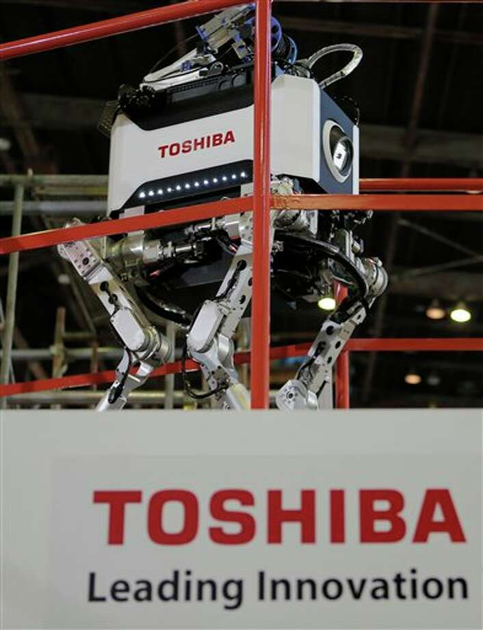 Toshiba Corp.'s nuclear inspection robot walks on a stage during a demonstration at a Toshiba factory in Yokohama, west of Tokyo, Wednesday, Nov. 21, 2012. The four-legged robot is designed to help at the meltdown-crippled Japanese nuclear plant, climbing over debris and venturing into radiated areas off-limits to human workers. (AP Photo/Itsuo Inouye) Photo: Itsuo Inouye, ASSOCIATED PRESS / AP2012