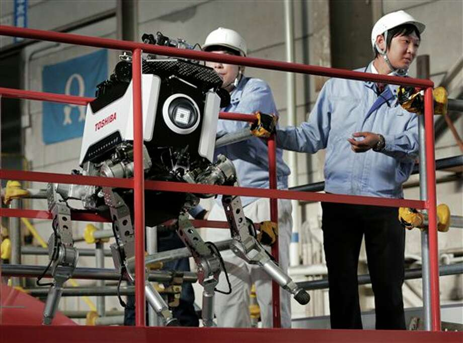 Toshiba Corp.'s nuclear inspection robot breaks down as its staff look on during a demonstration at a Toshiba factory in Yokohama, west of Tokyo, Wednesday, Nov. 21, 2012. The four-legged robot is designed to help at the meltdown-crippled Japanese nuclear plant, climbing over debris and venturing into radiated areas off-limits to human workers. The robot took a jerky misstep during a demonstration to reporters, freezing with one leg up in the air. It had to be lifted by several people and rebooted. (AP Photo/Itsuo Inouye) Photo: Itsuo Inouye, AP / AP