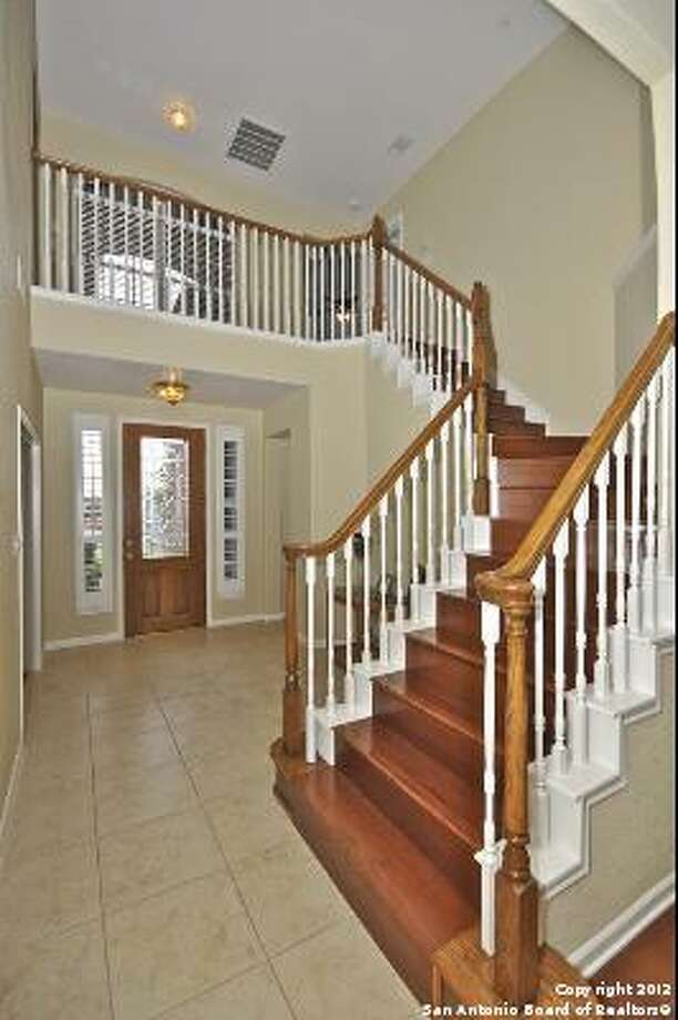 An elegant staircase reels down from the second floor to greet the visitor.
