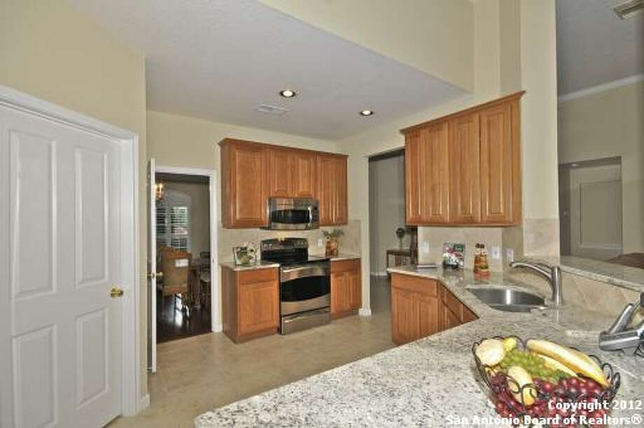 The kitchen offers granite countertops and lots of space with its large wood cabinets.