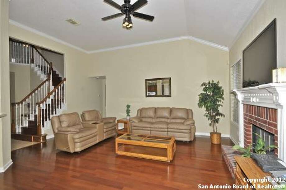 Adjoining the foyer is the spacious family room with cherry wood floors and a brick fireplace.