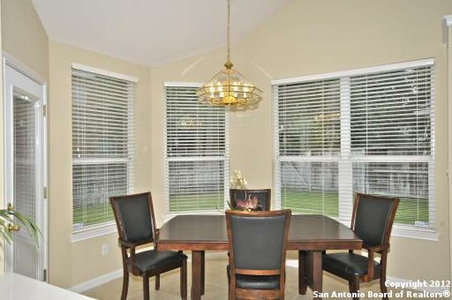 The breakfast nook enjoys a plethora of windows, providing a sunny area to enjoy meals.