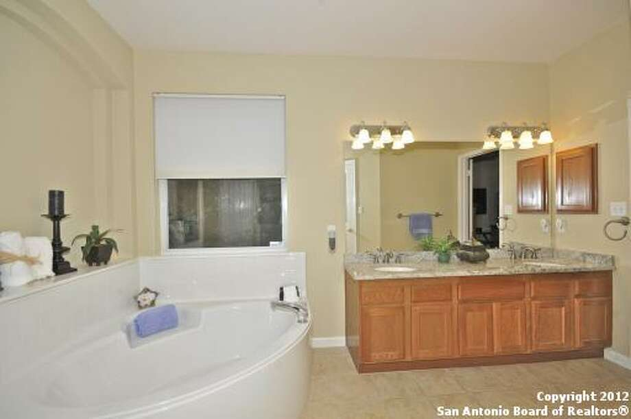 Adjacent to the deep soaking tub in the master bath is the vanity with dual sinks and a large mirror.