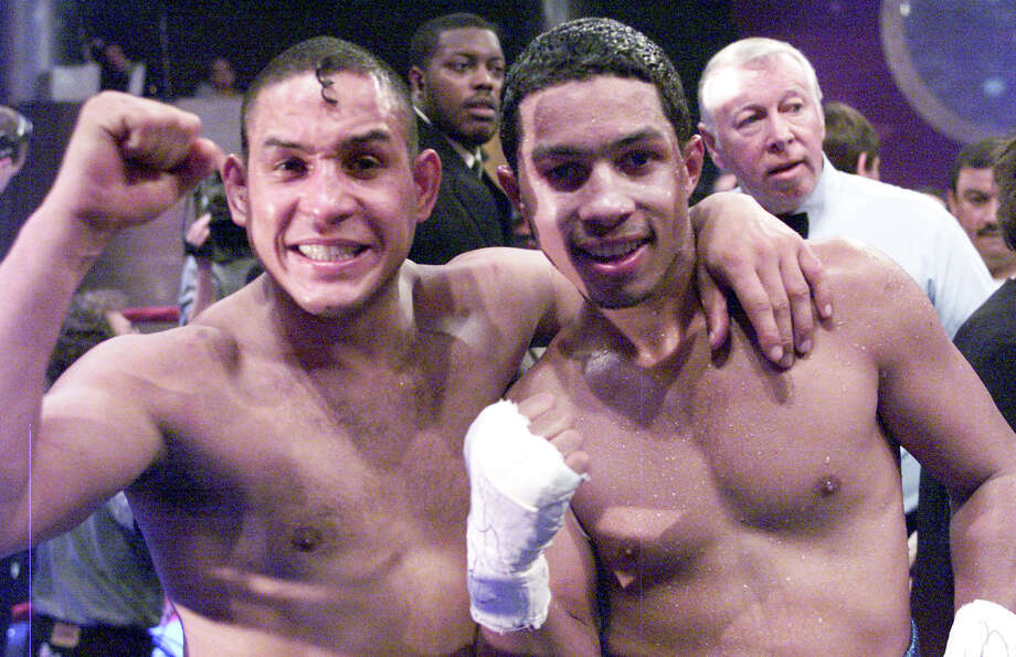 Hector Camacho Sr., left, poses with his son Hector Camacho Jr., as they celebrate after Camacho Jr. won his 12-round fight against Rocky Martinez at a nightclub in Miami Beach, Fla., Saturday, Feb. 3, 2001. The elder Camacho won his fight, too, a unanimous decision over Troy Lowry. Photo: GARY I. ROTHSTEIN, AP / AP