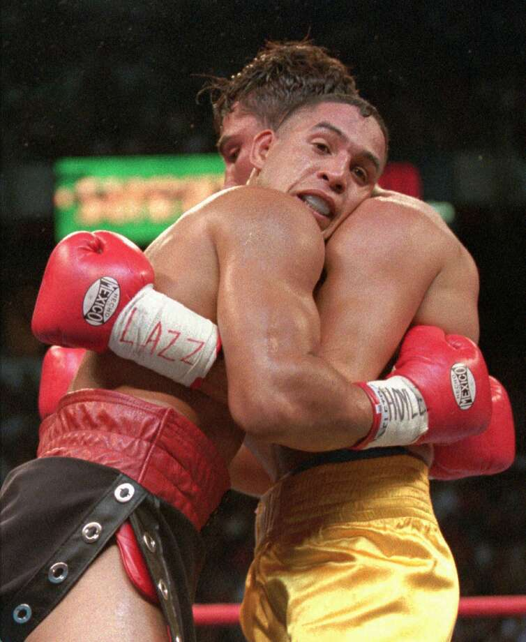 Hector Camacho, left, hangs onto Oscar De La Hoya during the second round of their WBC welterweight championship fight Sept. 13, 1997, in Las Vegas. Photo: MIKE SALSBURY, AP / AP