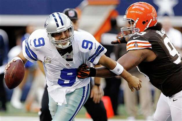 Dallas Cowboys quarterback Tony Romo (9) escapes a tackle attempt by Cleveland Browns' John Hughes (93) in the second half of an NFL football game, Sunday, Nov. 18, 2012, in Arlington, Texas. (AP Photo/Brandon Wade) Photo: Brandon Wade, Associated Press / FR168019 AP