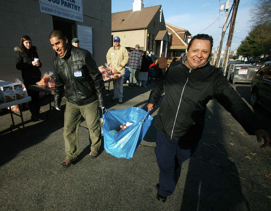 Volunteer Alfredo Perez, left, helps Ingrid Rosas of Bridgeport carry a heavy bag of Thanksgiving dinner items, including a frozen turkey, at the Black Rock Food Pantry's annual distribution on Wednesday, November 21, 2012. Photo: Brian A. Pounds / Connecticut Post