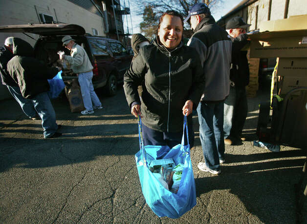 Ingrid Rosas, of Bridgeport, smiles after receiving a bag of Thanksgiving dinner items, including a frozen turkey, at the Black Rock Food Pantry's annual distribution on Wednesday, November 21, 2012. Photo: Brian A. Pounds / Connecticut Post