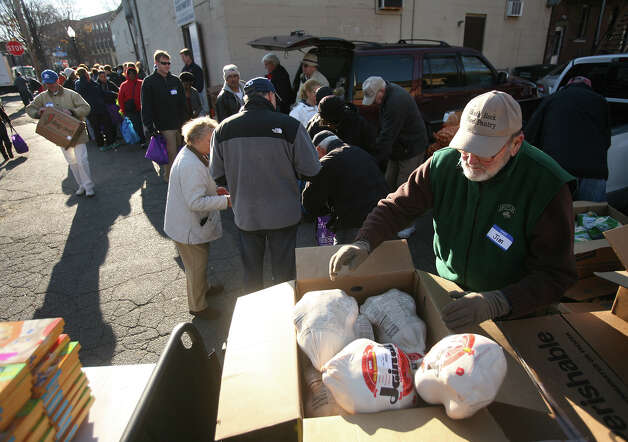 Volunteer Jim Casy, right, of Bridgeport, unpacks boxes of frozen turkeys as hundreds wait in line during the Black Rock Food Pantry's annual distribution in Bridgeport on Wednesday, November 21, 2012. Photo: Brian A. Pounds / Connecticut Post