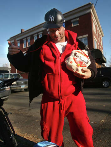 David Baerga of Bridgeport prepares to load a frozen turkey into his backpack at the Black Rock Food Pantry's annual distribution in Bridgeport on Wednesday, November 21, 2012. Photo: Brian A. Pounds / Connecticut Post