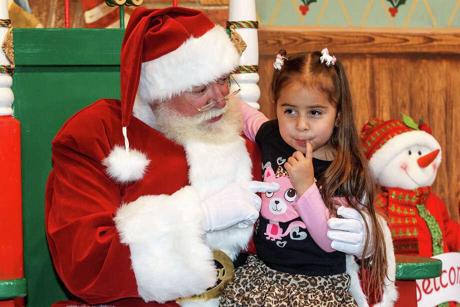 "Three-year-old Baylia Lopez isn't sure what to ask Santa for during their visit  at Santa's Living Room at Morgan's Wonderland's new ""A Wonderland Christmas.""  Photo: Marvin Pfeiffer, San Antonio Express-News / Express-News 2012"
