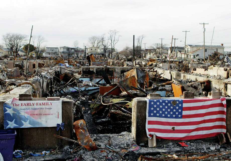 A U.S. flag is draped amidst rubble left by a fire during Superstorm Sandy, Tuesday, Nov. 20, 2012, at Breezy Point in the Queens borough of New York. New York City alone has already removed an estimated 271,000 tons of wreckage from flooded neighborhoods. Photo: Frank Franklin II, AP / AP