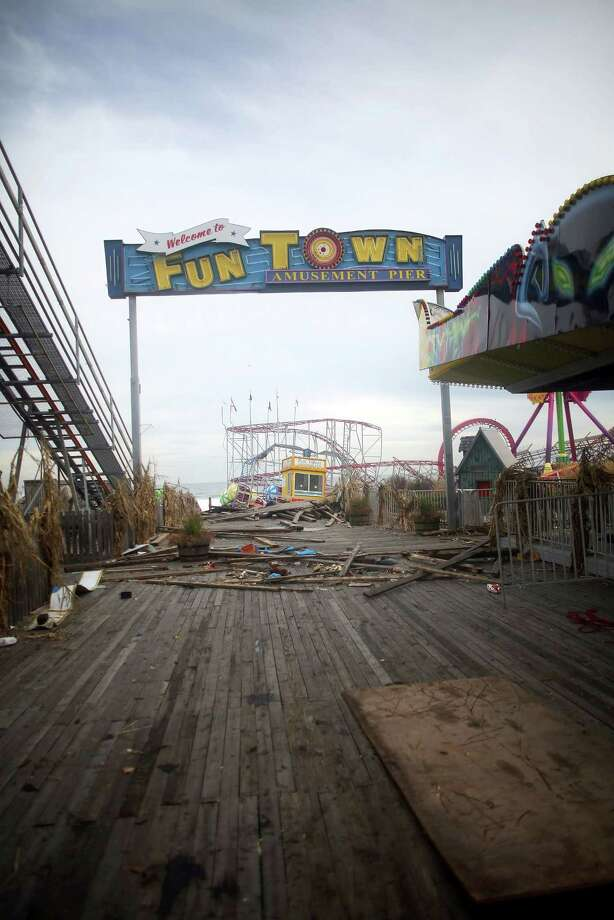 SEASIDE HEIGHTS, NJ - NOVEMBER 16:  A sign stands above the heavily damaged Funtown Pier on November 16, 2012 in Seaside Heights, New Jersey. Two amusement piers and a number of roller coasters were destroyed in the seaside town by Superstorm Sandy.   (Photo by Mario Tama/Getty Images)  *** BESTPIX *** Photo: Mario Tama, Getty Images / 2012 Getty Images